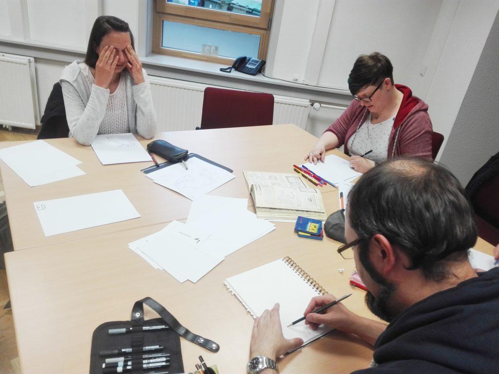 Gruppe aus 4 Leuten arbeitet am Tisch. Eine Frau hält sich die Augen zu, die anderen zeichnen konzentriert etwas.