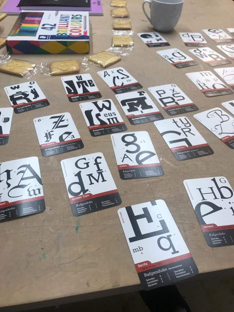 Karten A7 mit je einer anderen Schrift verteilt auf Tisch