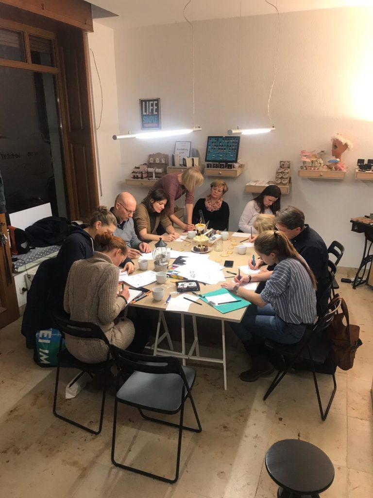Gemütlicher Raum mit Holzdielen und großem Schaufenster. Draußen ist es dunkel, aber innen brennt warmes Licht. An einem großen Tisch sitzen die Teilnehmer und arbeiten alleine konzentriert an ihren Werken. Annett bei einer von ihnen und berät.