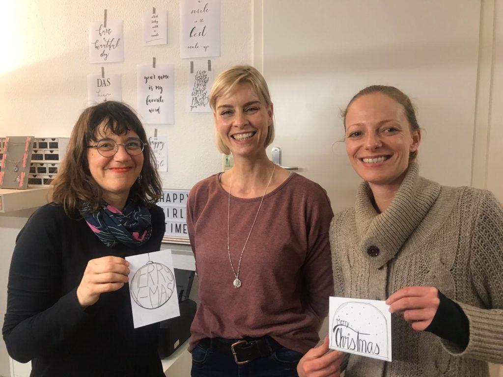Annett Gerhardt zwischen uns Organisatorinnen (Franziska Hagen und Simone Fass). Wir lächeln in die Kamera und Simone und Franzi halten selbst gestaltete Karte hoch.